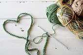 A close up image of a green crochet heart symbol and three skeins of yarn.