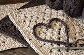 A close up image of a brown crochet heart symbol on top of brown and beige dishcloths.
