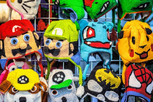 häkeln sie strickmützen in verschiedenen comic-figuren auf dem display an weihnachtsmarkt im winter-wunderland - kindermütze häkeln stock-fotos und bilder