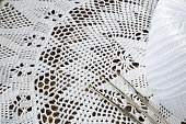 A close up image of a white lace crochet doily and three metal crochet hooks.