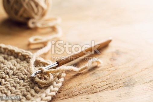 Close up young woman crocheting with needle and wool