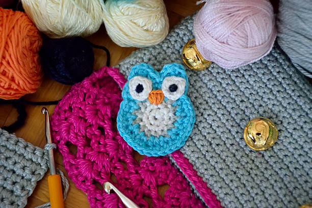 crochet small blue owl on colorful background - handtasche eule stock-fotos und bilder