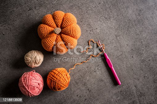 Crochet pumpkin, hook and cotton yarn balls on dark grey background. Top view photo. Hobby