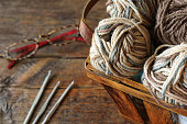 A close up image of crochet yarn and crochet hooks on a vintage wooden table.