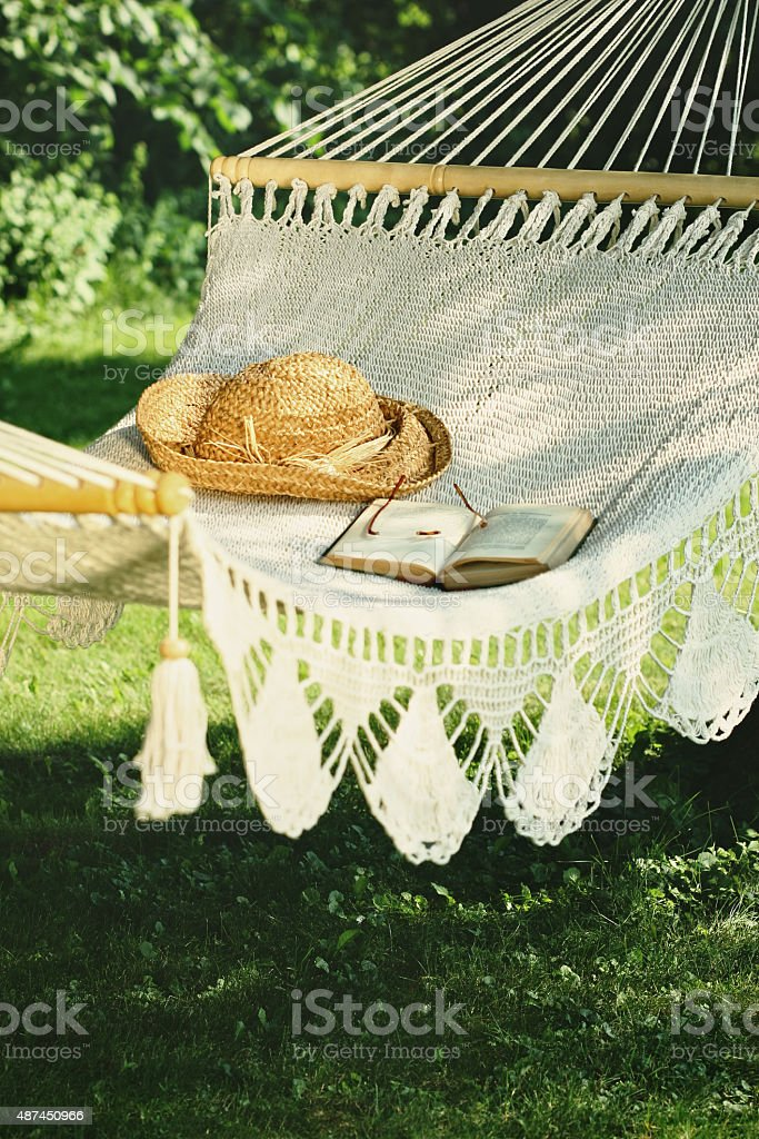 Crocheted hammock with straw hat and book stock photo