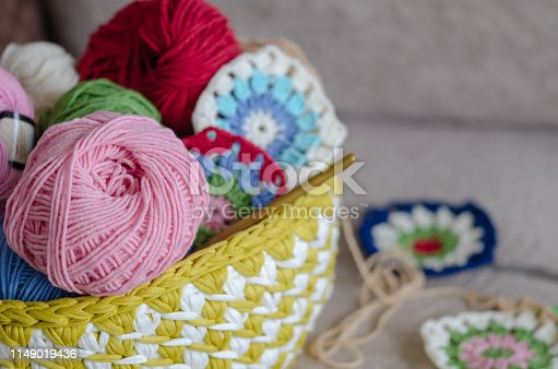 Multicolored plaid squares of crocheted on a cream colored seat background