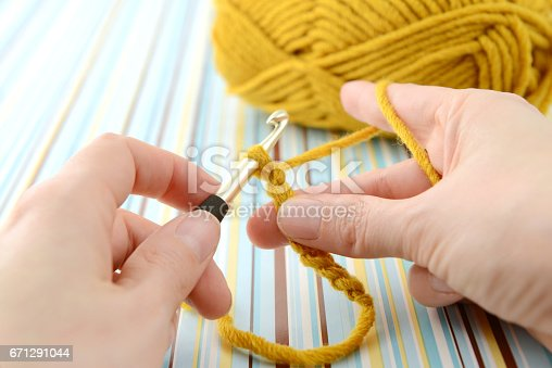 Crochet hook on wooden background