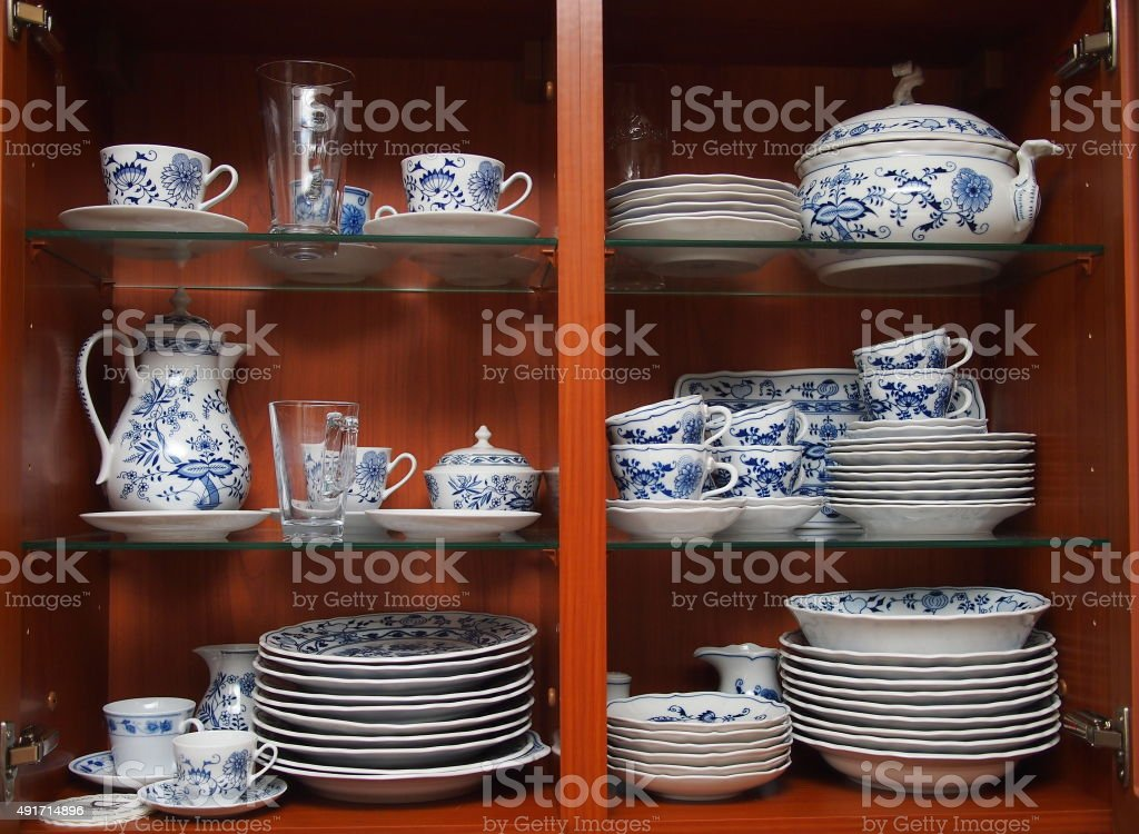 Crockery in wooden kitchen cabinet stock photo