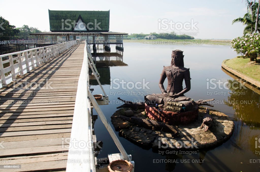 Crocodile statue name Chalawan at front of pavilion in lake stock photo