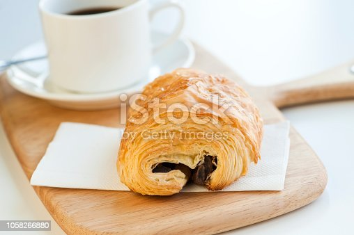 fresh pain au chocolate and cup of coffee on the table
