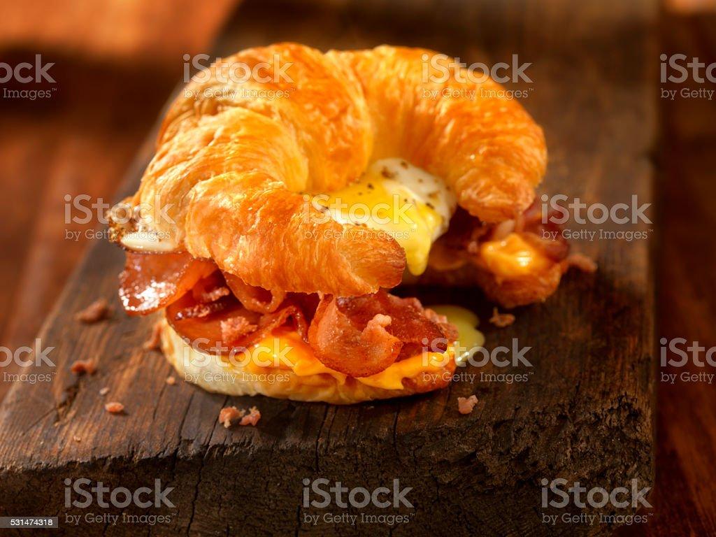 Prima colazione al mattino presto con Cornetto Panino con pancetta, uova e formaggio - foto stock
