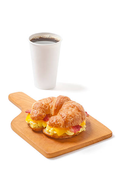 Croissant Breakfast Sandwich with Egg, Cheese, Bacon and Coffee stock photo