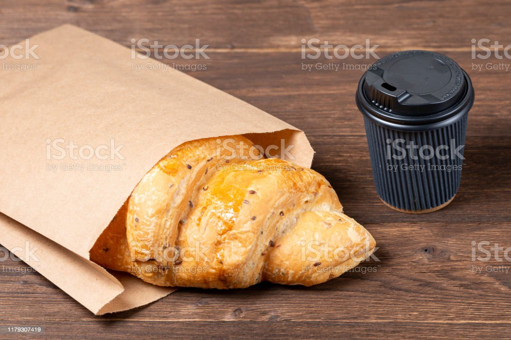 croissant in paper bag on wooden background with paper disposable cup of coffee. concept of continental breakfast and eco packaging croissant in paper bag on wooden background with paper disposable cup of coffee. concept of continental breakfast and eco packaging Bag Stock Photo