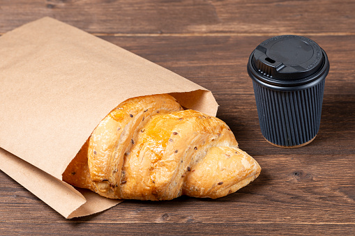 Croissant In Paper Bag On Wooden Background With Paper Disposable Cup Of Coffee Concept Of Continental Breakfast And Eco Packaging Stock Photo - Download Image Now