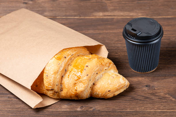 croissant in paper bag on wooden background with paper disposable cup of coffee. concept of continental breakfast and eco packaging stock photo