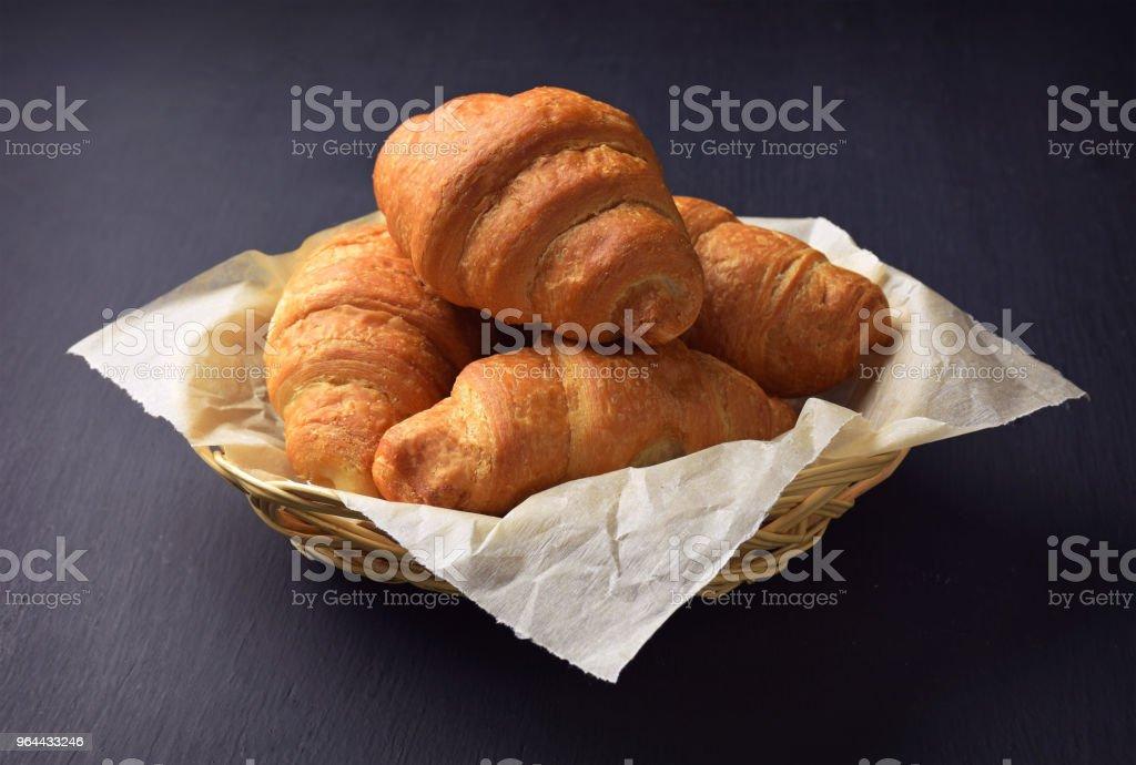 croissant na mesa. Croissant close-up sobre um fundo preto.  Pedaços de chocolate e doce bolos caseiros. - Foto de stock de Assado no Forno royalty-free