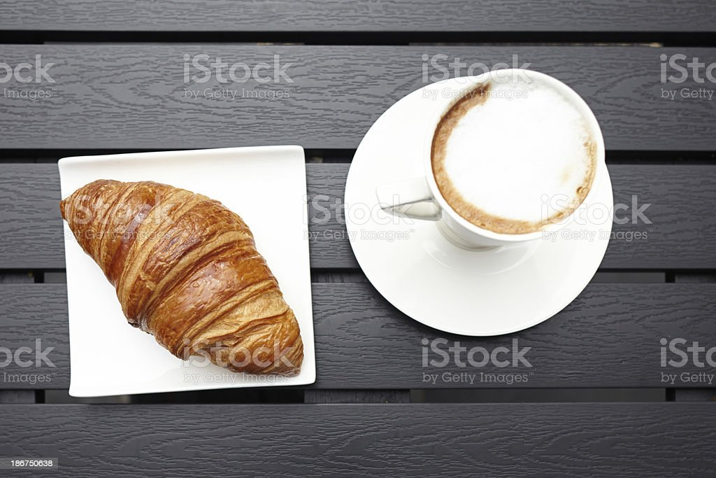 Croissant pastry with cappuccino drink on table top view royalty-free stock photo