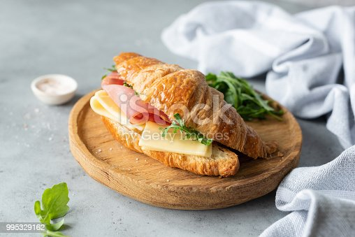 Croissant sandwich with cheese, ham and arugula on wooden cutting board, gray concrete background. Selective focus. Tasty breakfast sandwich or snack