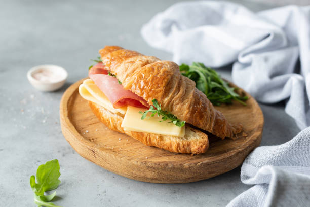 Croissant sandwich with cheese, ham and arugula Croissant sandwich with cheese, ham and arugula on wooden cutting board, gray concrete background. Selective focus. Tasty breakfast sandwich or snack croissant stock pictures, royalty-free photos & images
