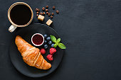 istock Croissant with berries, jam and cup of black coffee on black background 1001971962