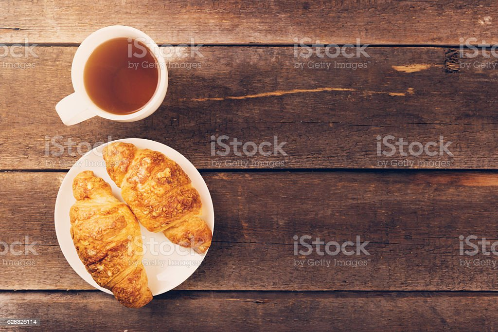 croissant with cup of tea on wooden table. copy space stock photo