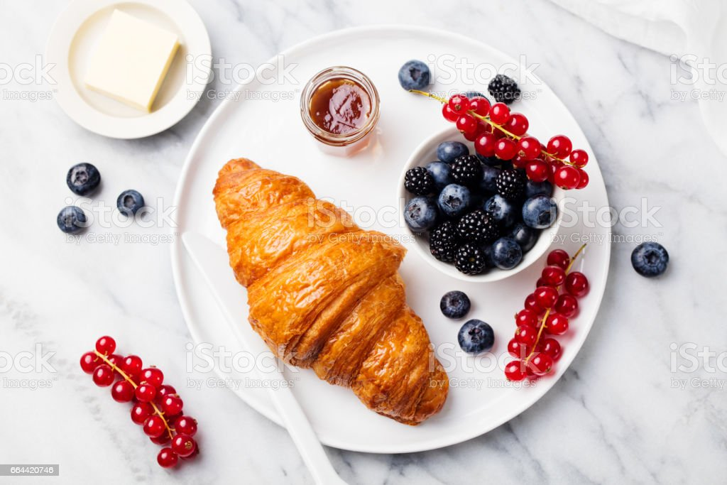 Croissant with fresh berries and butter on a marble texture background. Top view