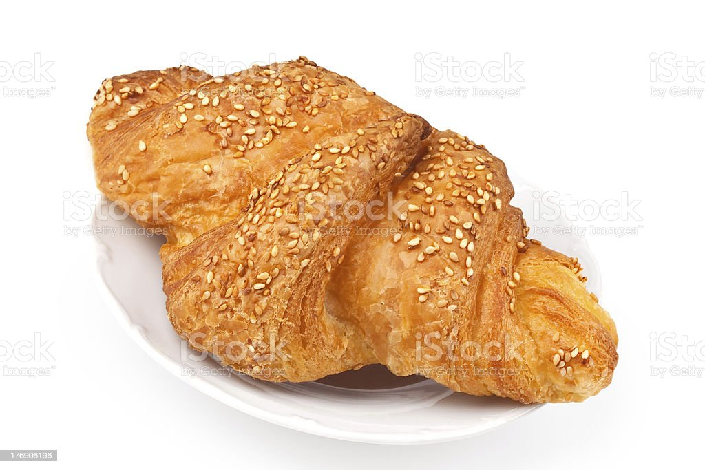 Croissant with sesame seeds on a plate stock photo