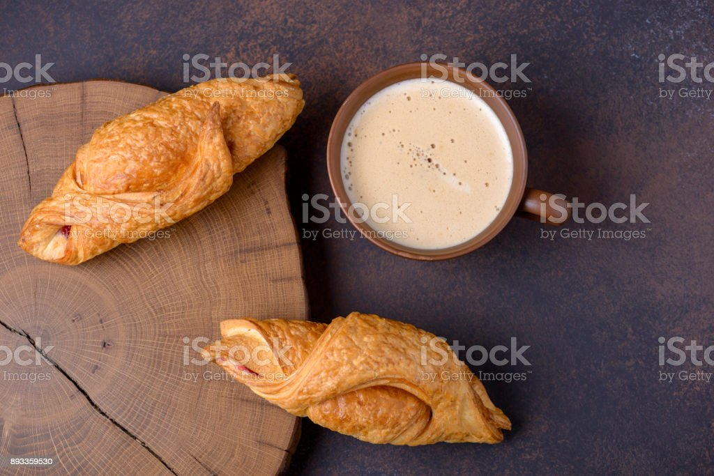 Croissants and coffee on brown background stock photo
