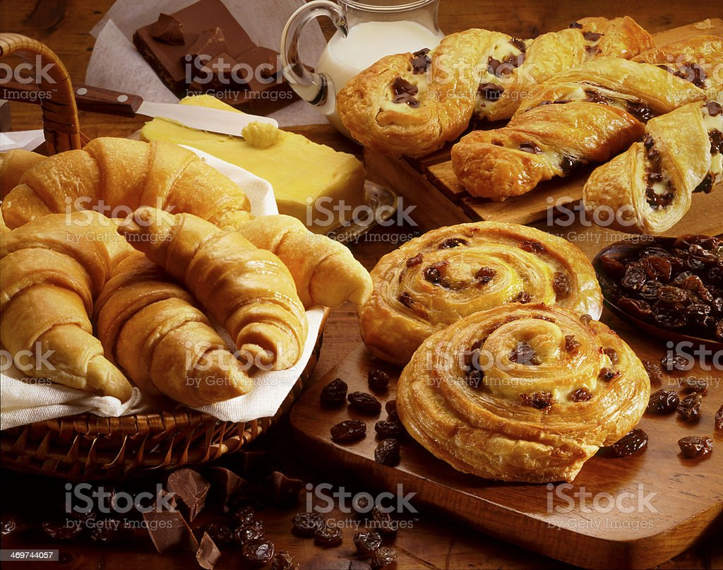 Croissants and pastries in baskets and on wooden surfaces stock photo
