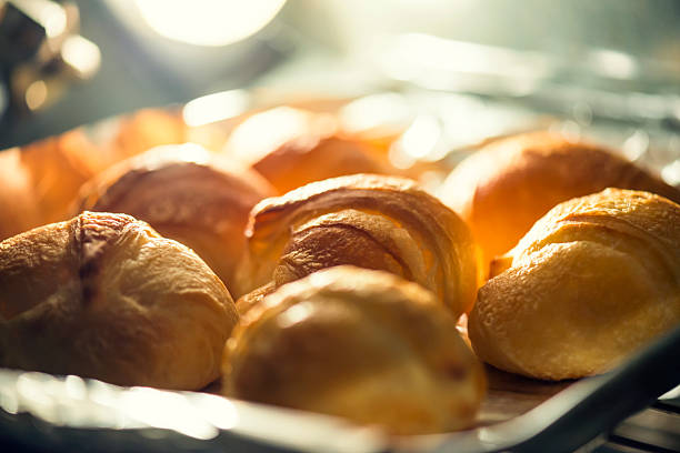 Croissants baking in the oven Croissants baking in the oven. Light source if the light bulb in the oven.Shallow depth of field. baking bread stock pictures, royalty-free photos & images