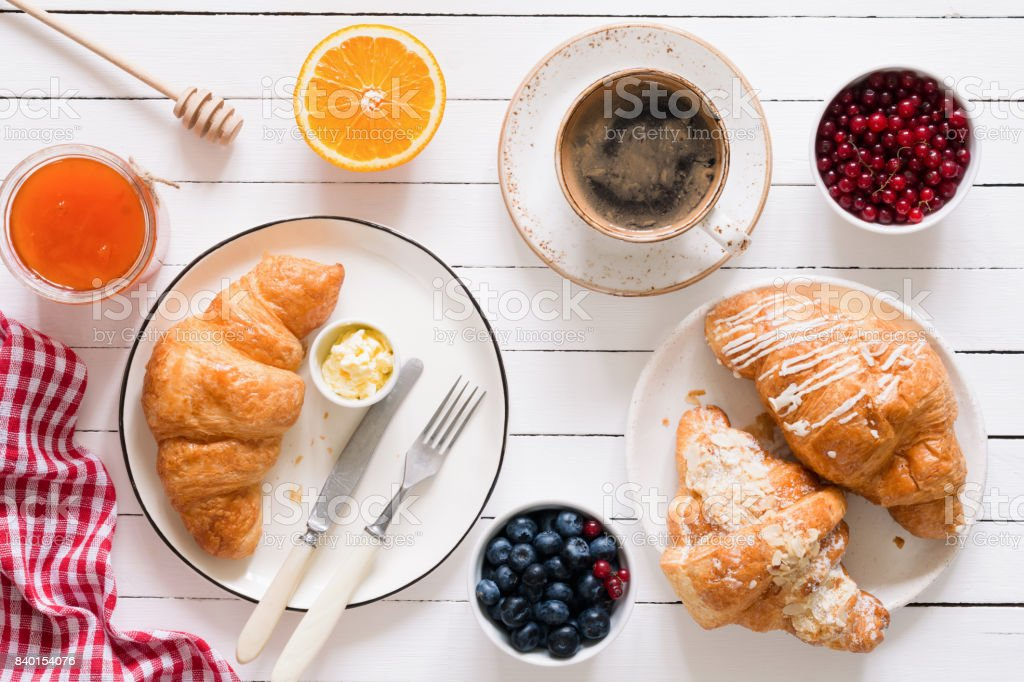 Croissants, coffee, jam and fruits. Continental breakfast table top view stock photo