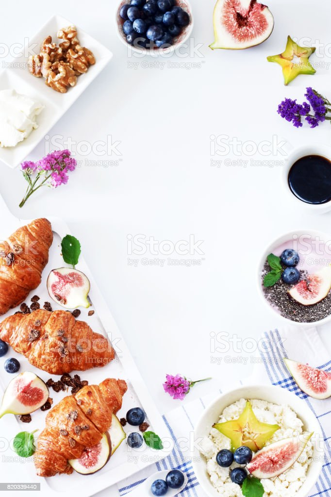Croissants, cottage cheese, yogurt, blueberry, figs, starfruit and walnut and black coffee. stock photo