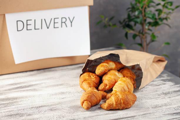 Croissants in einer Papiertüte. Lebensmittellieferung Online-Bestellung. Quarantänekonzept. – Foto
