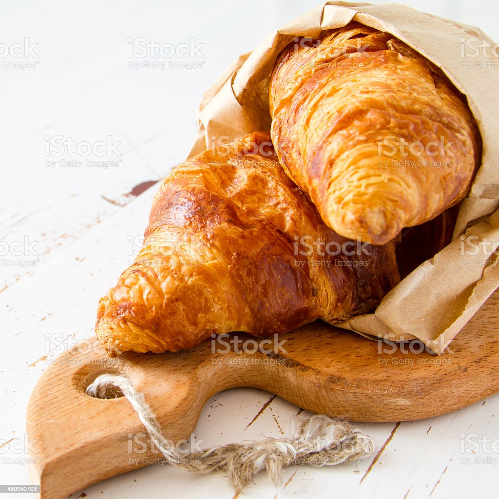 Croissants in paper bag on white wood background stock photo