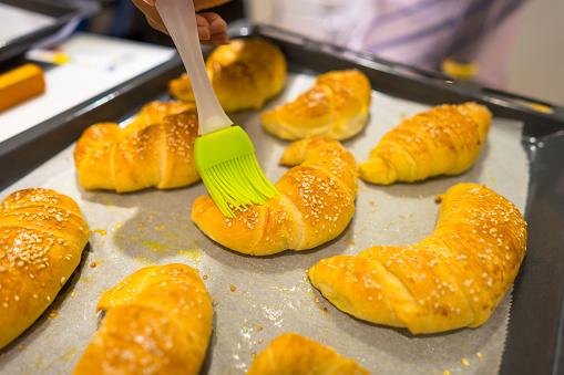 Croissants Haciendo Y Cepillado Con Huevo En Bandeja Y Papel De La Hornada Foto de stock y más banco de imágenes de Al horno