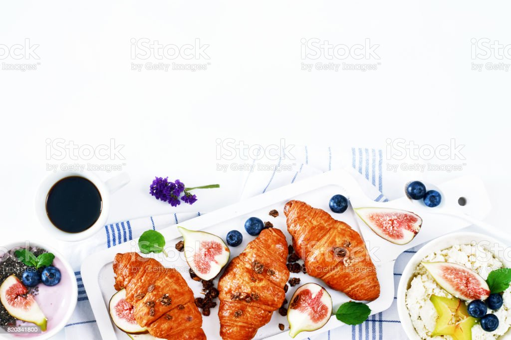 Croissants on board, bowl of cottage cheese, yogurt with chia seeds, fresh fruit and berry, espresso on a white table. stock photo