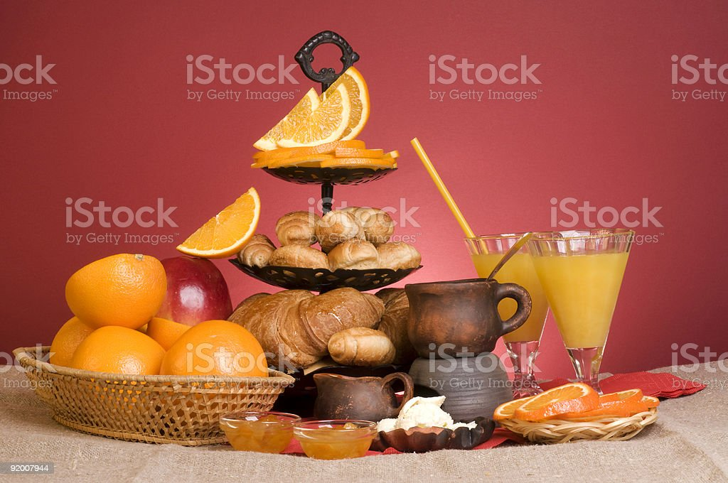 Croissants, orange, butter, apple, plate and glasses. royalty-free stock photo