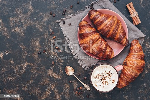 istock Croissants with coffee on a dark surface, top view, copy space. 995524364