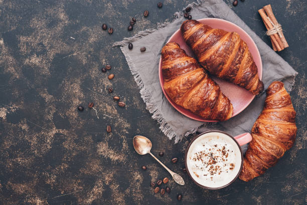 Croissants with coffee on a dark surface, top view, copy space. Croissants with coffee on a dark surface, top view, copy space croissant stock pictures, royalty-free photos & images