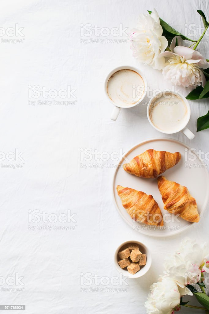 Breakfast on white flat lay. Croissants with cup of coffee and flowers