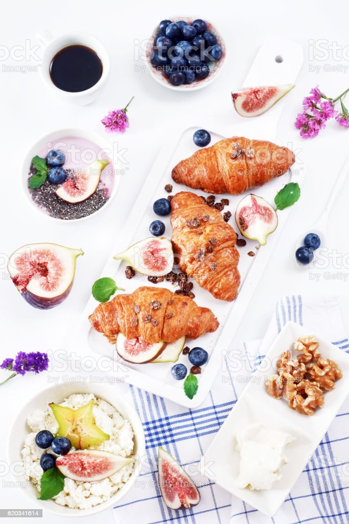Croissants, yogurt, black coffee, ricotta with fresh fruit, berry and flowers on white table. stock photo