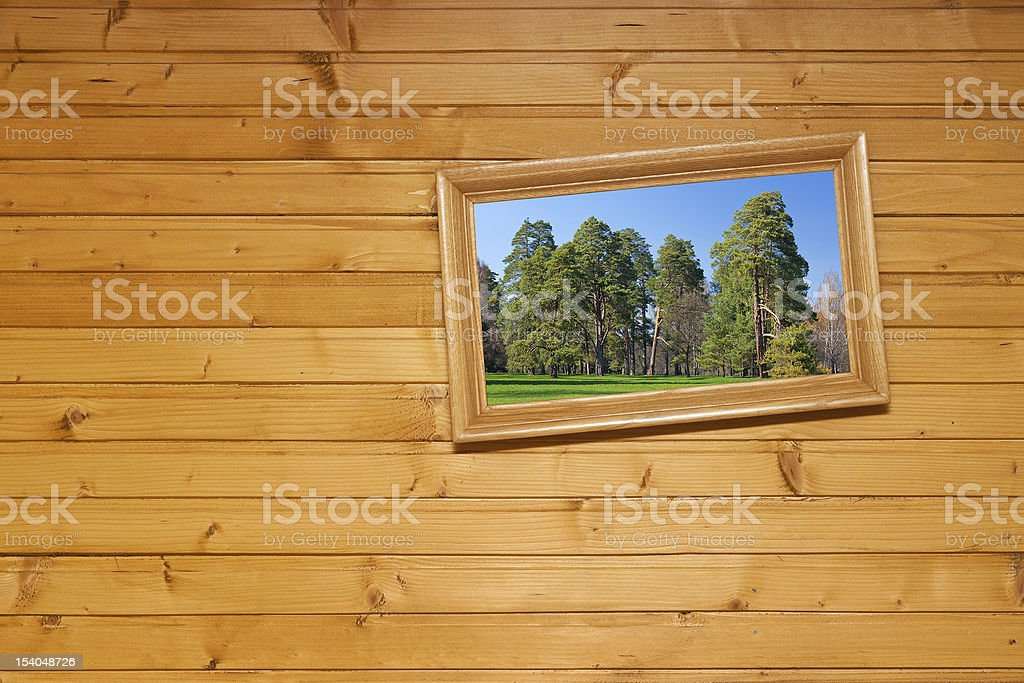 Crooked picture hanging on the wooden wal stock photo