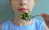 Crop close up shot of girl eating salad