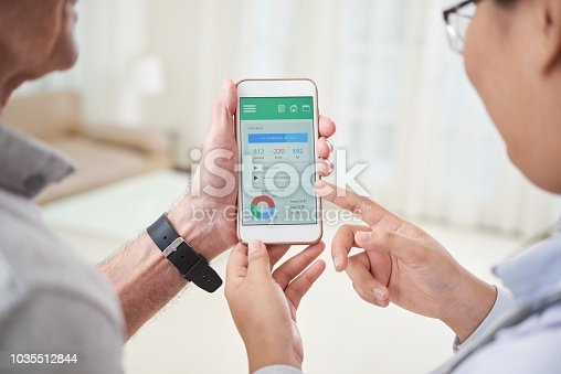 istock Crop doctor and patient looking application on smartphone 1035512844
