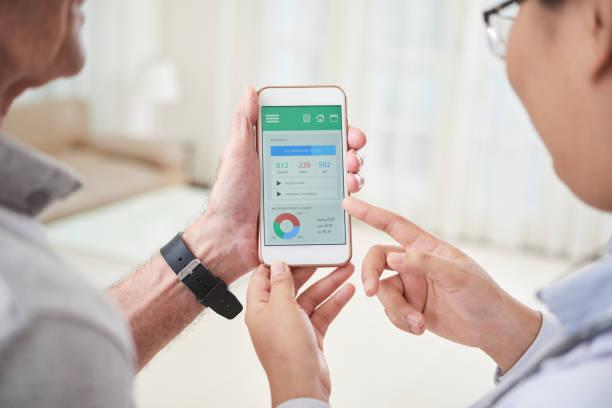 colheita médico e paciente, procurando o aplicativo no smartphone - app - fotografias e filmes do acervo