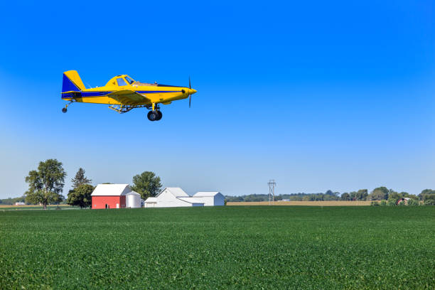 Crop duster flying over farmland stock photo