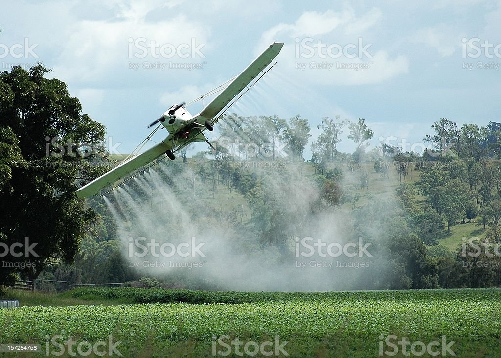Crop duster plane banking over a field while spraying stock photo