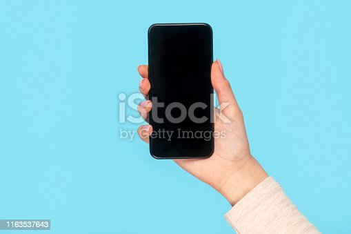 Crop female hand holding contemporary smartphone of black color on blue background