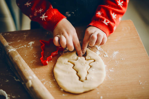 crop kid cutting christmas cookies - christmas cooking foto e immagini stock