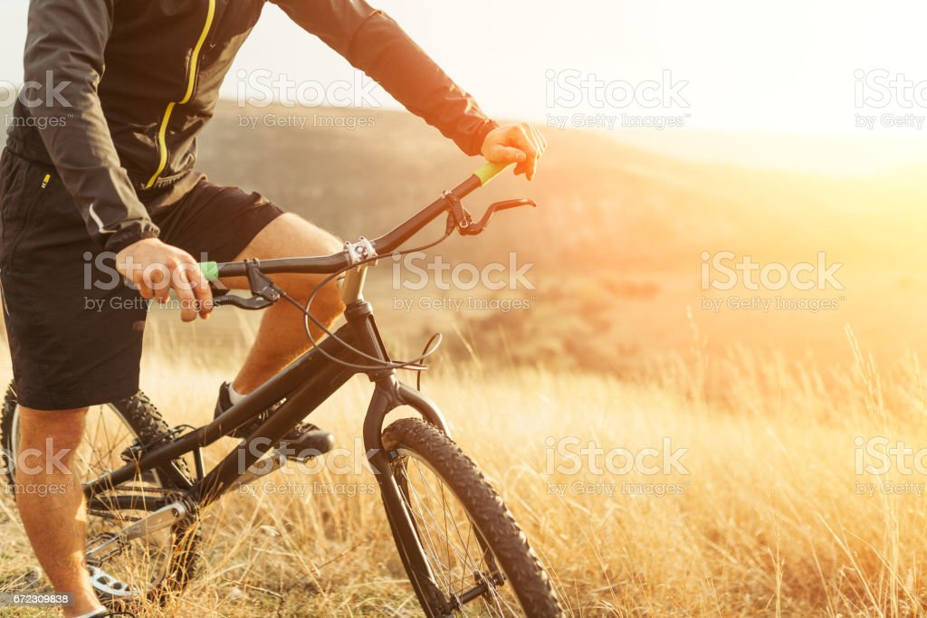 Crop male riding bicycle stock photo